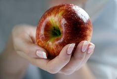Apple in a female hand Royalty Free Stock Photo