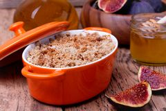 Apple and figs crumble on wooden background. Apple and figs crumble  in orange ceramic dish  with honey on wooden background Royalty Free Stock Photography