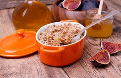 Apple and figs crumble on wooden background. Apple and figs crumble  in orange ceramic dish  with honey on wooden background Royalty Free Stock Photos