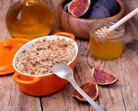 Apple and figs crumble on wooden background. Apple and figs crumble  in orange ceramic dish  with honey on wooden background Stock Image