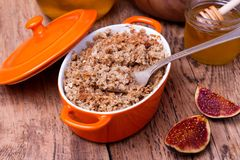 Apple and figs crumble on wooden background. Apple and figs crumble  in orange ceramic dish  with honey on wooden background Royalty Free Stock Photo