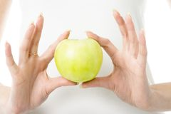 Apple in fingers. Green fresh apple in woman hands. Focused on apple. You Can put your logo or text on this apple Royalty Free Stock Photography
