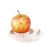 Apple fitness. A red apple resting on a coil of measurement tape, isolated against a white background stock images