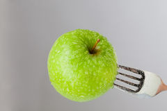 Apple on a fork Royalty Free Stock Images