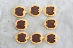 Apple a formé des biscuits disposés dans les rangées sur le fond texturisé par lumière, le plan rapproché, profondeur de champ, f Image stock