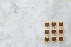 Apple a formé des biscuits disposés dans les rangées sur le fond texturisé par lumière, le plan rapproché, profondeur de champ, f Photo libre de droits