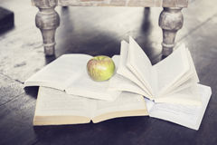 Apple and four open books on a floor Stock Images
