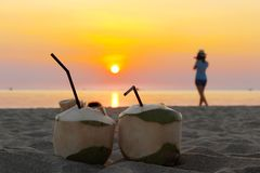 Apple-Fruchtcocktail auf dem Strand und einer Frau genießt den Sonnenuntergang lizenzfreie stockbilder