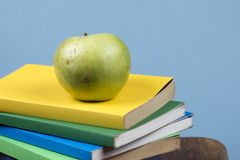 Apple fruit on top of a book stack, on the back of school classes. Apple fruit on top of a book stack, on the back of school classes stock photo