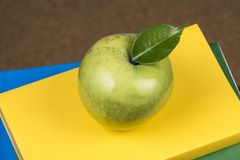 Apple fruit on top of a book stack, on the back of school classes. Apple fruit on top of a book stack, on the back of school classes stock image