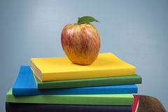 Apple fruit on top of a book stack, on the back of school classes. Red Apple fruit on top of a book stack, on the back of school classes royalty free stock images