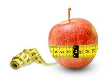 An apple full of strength and health measures its waist and is quite the result..Symbol of proper nutrition. royalty free stock photography