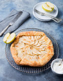 Apple galette, pie, tart with cinnamon on cooling rack on a blue stone background.  Royalty Free Stock Images
