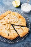 Apple galette, pie, tart with cinnamon on cooling rack on a blue stone background Top view. Apple galette, pie, tart with cinnamon on cooling rack on a blue Stock Photo