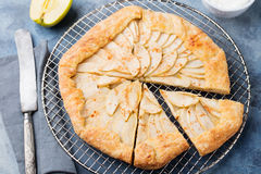 Apple galette, pie, tart with cinnamon on cooling rack on a blue stone background Top view. Apple galette, pie, tart with cinnamon on cooling rack on a blue Royalty Free Stock Photo