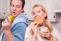 Apple gegen Krapfen-gesunde Essenentscheidung Stockbilder