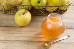 Apple-Gelee und -äpfel im Korb auf rustikalem Holztisch stockfotografie