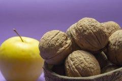 Apple, gemeenschappelijke okkernoten in natuurlijke kokosnotenshell kop royalty-vrije stock fotografie