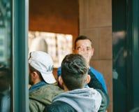 Apple Genius man wearing blue t-shirt welcoming customers Stock Photography