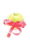 Apple gift. Green apple wrapped with red ribbon isolated on white background Stock Photos