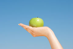 Apple in girl's hand over blue sky. Close-up of  apple in girl's hand over blue sky Royalty Free Stock Images