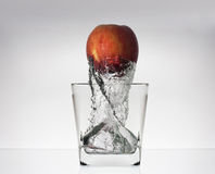 Apple in glas with water. Apple splash in glass of water isolated on white background Royalty Free Stock Photos