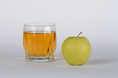 Apple with glass of juice. Green apple with the glass of juice on white background Stock Photography