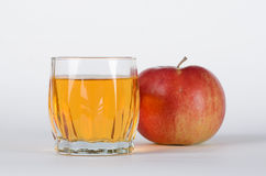 Apple with glass of juice. Red apple behind with the glass of juice on white background Royalty Free Stock Photo