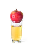 Apple in glass of juice. Red apple with drops in glass of juice Stock Photos