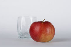 Apple with glass. Red apple forward to empty glass on the white background Royalty Free Stock Image