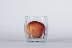 Apple in the glass. On white background Royalty Free Stock Image