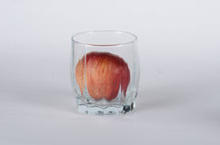 Apple in the glass. On white background Royalty Free Stock Photos