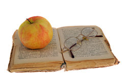 Apple and glasses on the book Stock Photos
