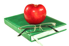 Apple and glasses on a book Stock Photo