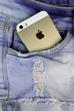 Apple Gold iPhone 5s in a blue denim pocket Stock Photo