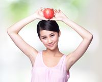 Apple is good for health. Beautiful young woman hold red apple with charming smile. Isolated over nature green background, asian beauty Stock Photography