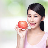 Apple is good for health. Beautiful young woman hold red apple with charming smile.  over nature green background, asian beauty Royalty Free Stock Photography