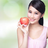 Apple is good for health. Beautiful young woman hold red apple with health teeth. Isolated over nature green background, asian beauty Stock Image