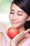 Apple is good for health. Health lifestyle concept - Beautiful young woman hold red apple with smile. Isolated over nature green background, asian Royalty Free Stock Photos