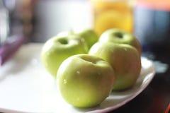 Apple, grüne Äpfel auf einer Platte, in den Wassertropfen Lizenzfreie Stockbilder