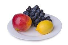 Apple grape lemon on a plate Royalty Free Stock Photos