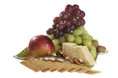 Apple, grape, nuts and cheese lying on a plate. royalty free stock photography
