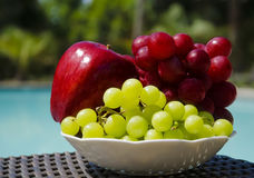 Apple and grape by the swimmimg pool. Red apple and grape in white plate on table by the swimming pool Royalty Free Stock Photos