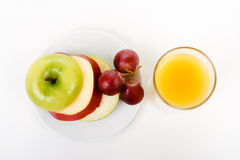 Apple, grapes on a plate and a glass of orange juice Stock Photography