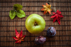 Apple green autumn leaves on wooden background. Apple green wooden brown background plumautumn leaves Stock Photos