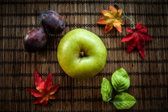 Apple green autumn leaves on wooden background. Apple green wooden brown background plumautumn leaves Royalty Free Stock Image