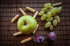 Apple green autumn leaves on wooden background. Apple green green grapes  plum autumn rusk Royalty Free Stock Image