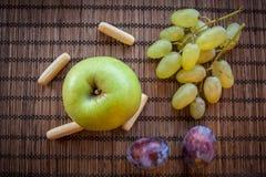 Apple green grapes green plum and rusk. Green Apple grapes plum and rusk on wooden background Stock Photos