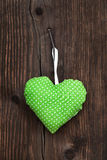 Apple green handmade fabric heart with polka dots hanging on an. Old wooden background. Idea for a greeting card Royalty Free Stock Photography