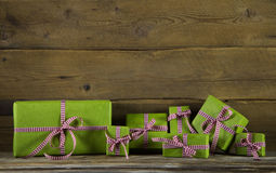 Apple green presents with red and white checked ribbon on wooden Royalty Free Stock Photos